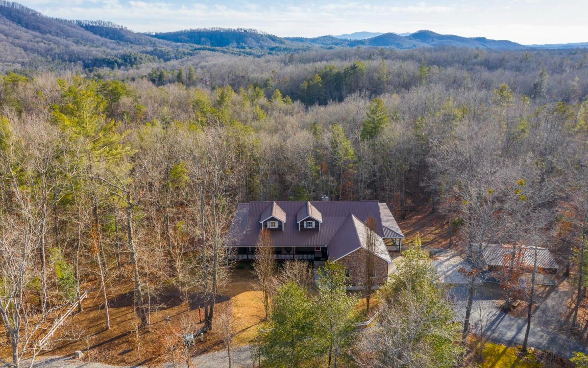 This Private, Peaceful, Mountain Retreat w/exceptional 4BR/3.5 BA Log Sided Home is situated on 6.48 acres of stunning woodlands with Seasonal Mtn Views. In addition to the 5016 SF home & attached 2 Car Garage, the property includes a 2 car carport & 30X40 Metal Bldg. The home's unbelievable charming interior offers a special ambiance the second you cross the threshold; including a massive stacked stone wood burning fireplace & rustic log beams spanning the vaulted ceiling in the Great room; Custom Cabinets & Counter tops; Attractive kitchen w/all the bells & whistles; Separate Pantry, Laundry & Office & 3 gas log fireplaces; Full finished terrace level complete w/family room, Full kitchen, Bedroom & Bath, Exercise Room & 3 add'l finished rooms to suit. The home is surrounded by 5144 SF of 10 ft wide covered porches overlooking so much outdoor beauty. The combination of this entire mesmerizing property can not be imagined, so come see for yourself!