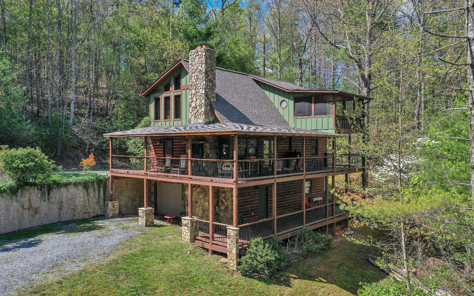 LOCATION< LOCATION< LOCATION!!! Aska Adventure Area with deeded Toccoa River Access. Why drive for 30 minutes to get to your cabin when you can be there in less than 10 minutes from either Downtown Blue Ridge or Lake Blue Ridge and within walking distance to the Toccoa River. 3 Bedroom / 3 Bath + Large Loft with large fixed glass windows to give you plenty of sunlight making this cabin a true gem. Oversized covered porches, Screen Porch off Master Bedroom, Floor to Ceiling Stone Covered Wood Burning Fireplace with the center stone the shape of Georgia. Chimney has a Triple Flue venting system for Fireplace, Outside Grill (on the covered porch) & Wood Stove in Basement. 2 driveways for your convenience, park up top with your groceries or park in the 1 car garage to enter thru the basement. Roof is less than 1 year old. (Gutters have not been replaced yet but will be).